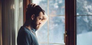 homem-com-sintomas-de-depressão-olhando-pela-janela